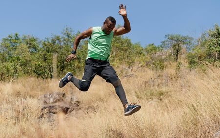 African american man athlete runner exercise training and jumping  outdoors in beautiful mountain nature landscape. Active health and motivation lifestyle and Adventure Concept