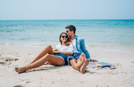 Happy young romantic couple in love sitting and kissing on the Beach. Young couple in honeymoon having holidays on exotic beach.