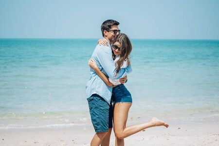 Romantic couple having fun on the beach. Happy young romantic couple in sunglasses running on the beach, man hug and spin around his woman. Two tourists lovers on honeymoon travel enjoying summer vacation.