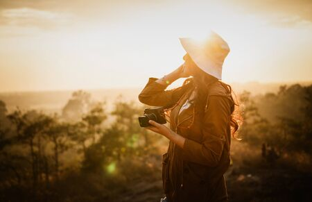 Portrait of young Asian woman traveler with backpack and hat standing on cliff's edge and taking a photo enjoying a beautiful nature. Concept of woman solo travel and relaxation moment.