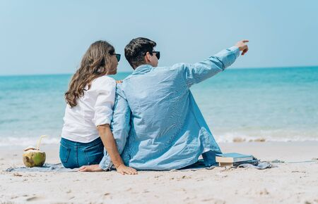 Back view of a couple sitting together on beach towel along the sea shore and pointing away out to sea. Romantic couple relaxing on the beach.