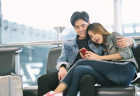Romantic couple in airport. Young Asain couple in casual wear using smartphone while sitting in the airport terminal waiting for boarding. Teenager are traveling and transportation with technology concept.