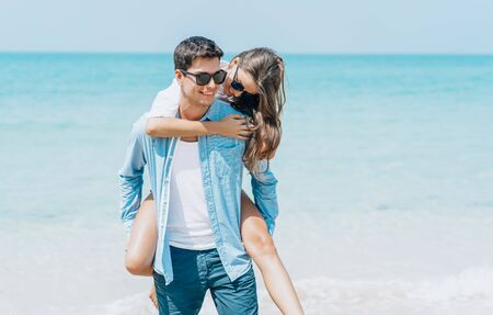 Handsome man giving piggy back to his girlfriend walking on beach behind blue sky or honeymoon trip. Beach couple laughing in love romance on travel honeymoon vacation summer holidays romance.