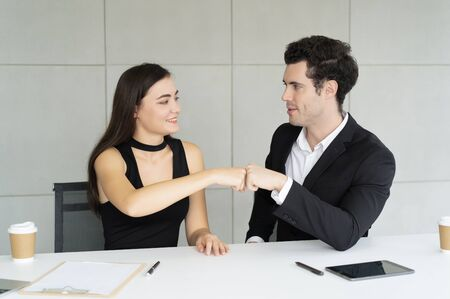 Proud couple making fist bump gesture. Two young age business workers smiling happy and confident. Working together with smile on face giving fist bump at the office.Teamwork concept.