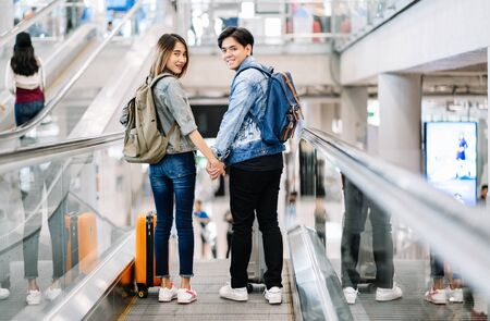 Happy loving Asian couple traveling with baggage getting down on the escalator to the departure area at the airport. Woman hold his hand and look back on camera and smile. Lover travel and transportation concept.