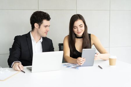 Beautiful young business woman and handsome businessman in formal suits discussing while using digital tablet in modern office.Busienss teamwork concept.