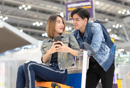 Romantic couple in airport. Young Asian couples are happy in the passenger Hall are ready for traveling while sitting on luggage trolley and using smartphone. Lover travel and transportation with technology concept