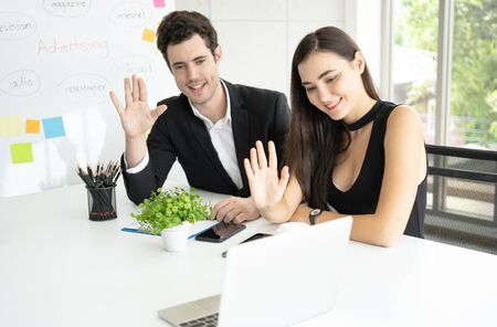 Beautiful young business woman and handsome businessman using a digital tablet and laptop  having video call talking and hi while sitting in modern office working together. Technology, communication and bueiness people concept. Banco de Imagens