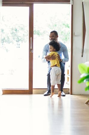 Happy family African American son running and hugging dad after going back from office. Welcome back home daddy and Sweet moments of fatherhood concept.