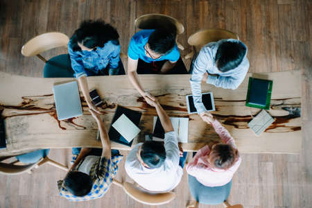 Top view of young people multiethnic diverse group handshake after meeting on top of desk. People and education teamwork concept Foto de archivo