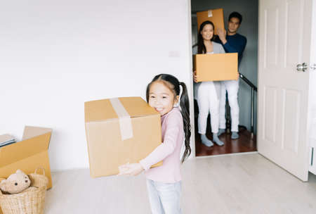 Portrait of a happy asian little daughter carrying boxes into the a new home on moving day. Happy Family move on a new home concept, helping parents with belongings, mortgage and relocation.