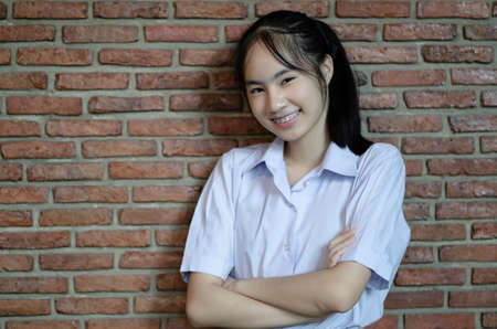 Portrait of smiling teenager in uniform standing with arms crossed at red brick wall and looking at camera.