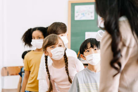 Multi-ethnic group of children with face mask stood in line let the teacher check, scan thermometer temperature for fever against the spread virus in classroom after covid-19 quarantine and lockdown.