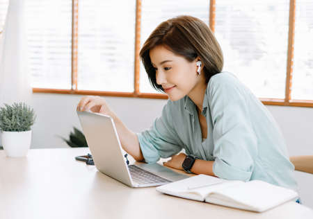 Happy young beautiful Asian woman using laptop working remote and wireless earphones sitting at table in home office.Remote work,E learning, New normal concept. 스톡 콘텐츠