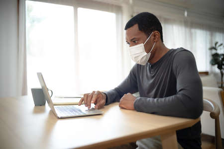 Portrait of handsome African American man with medical mask while working at desk at home during corona virus outbreak. Concept business people working at home,Remote,freelancer.COVID-19 epidemic. 免版税图像