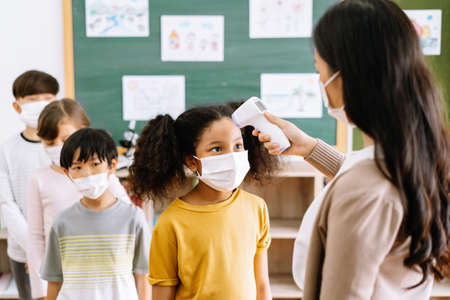 Group of Elementary School Pupils with face mask stood in line let the teacher check, scan thermometer temperature for fever against the spread virus in classroom after covid-19 quarantine and lockdown. 免版税图像