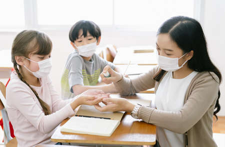 Female Asian teacher with protective face mask and sanitizing school children's hands with disinfectant spray in classroom after reopening school,covid-19 quarantine and lockdown.Healthcare concept.