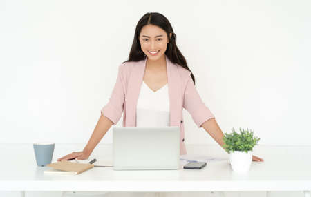 Portrait of smiling pretty young Asian business woman working small business online standing at workstation of desk and looking at camera. Freelance Startup Small business owner,Online selling. 免版税图像