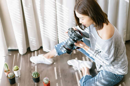 Beautiful young stylish Asian woman working indoors at home taking photo to cactus,plants with digital profressional camera.Happy Blogger,freelance work online marketing.Startup Small business owner.