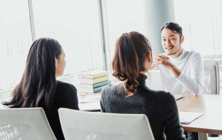 Portrait of attractive young Asian man team leader with colleagues workers sitting together in office boardroom. People job interview and Human resources concept.
