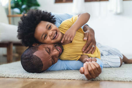 Black father in living room have a fun playing together on warm floor at home.Happy African family dad hugging, embracing his lovely child while lying on the floor.Sweet moments of fatherhood concept.