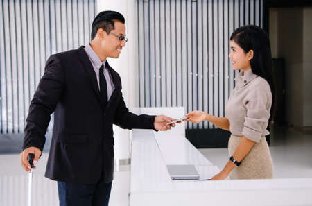 Young Asian handsome businessman arrive to hotel check in register information with woman receptionis at reception counter desk.Business travel concept.