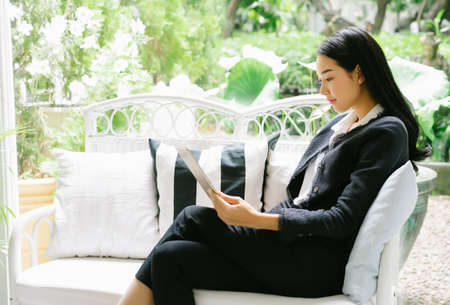 Beautiful young business woman using tablet, online shopping concept, freelance work in progress in modern white cafe garden interior in exterior. 免版税图像