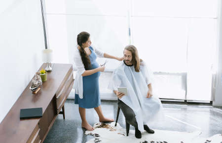 Beautiful pregnant woman cuts hair to handsome husband at home during quarantine coronavirus pandemic ,online hairdressing on tablet. New normal lifestyle Concept. Top view.