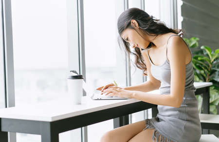 Portrait of young Asian casual woman working small business online working laptop in workspace and talking on cellphone during take a break drink coffee. Remote work at home and New normal concept.
