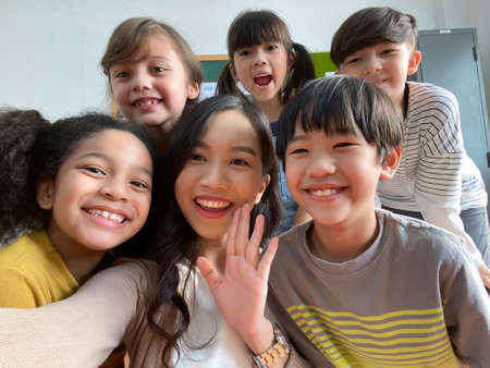 Smiling young Asian teacher making selfie with her schoolchildren in classroom. Elementary school,technology, children and people concept 免版税图像