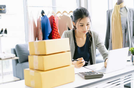 Portrait of young Asian woman fashion designer working small business online check her order in laptop computer for delivery to customer.SME, Delivery,Freelance Startup Home office, Shipping Concept.