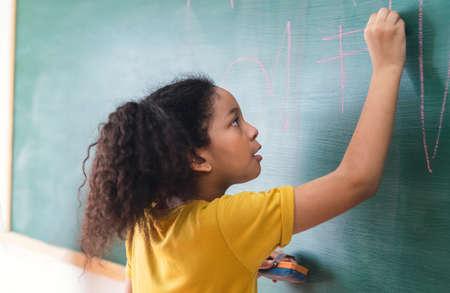 Afro american student girl writing on green chalkboard. Education, elementary school, learning, School children education concept. 免版税图像