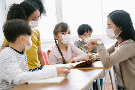 Group of Diverse Elementary School Pupils and Female Asian teacher wearing medical mask at elementary school.Teacher helping students in classroom.School reopen after covid-19 quarantine and lockdown.