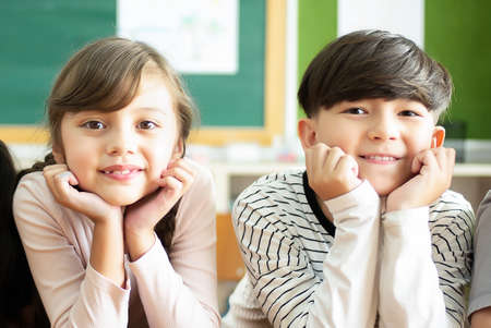 Back to school! Portrait of happy schoolchildren sitting on desk holding hand on chin and looking at camera in classroom.Education, elementary school,Childhood concept.