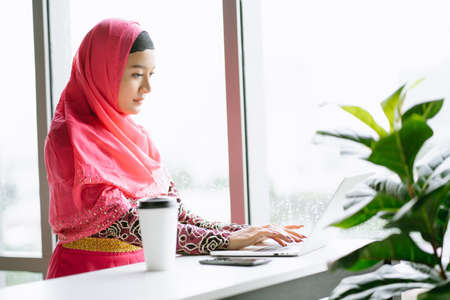 Portrait of young Muslim woman in hijab pink dress using laptop computer sitting at cafe table. Muslim business professional concept 免版税图像