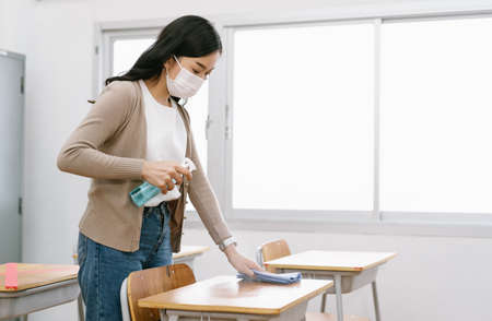 Young Asian female Teacher in a medical mask cleans up the desk in the classroom before students return to school after covid-19 quarantine and lockdown. Healthcare of pupils and students concept. 免版税图像