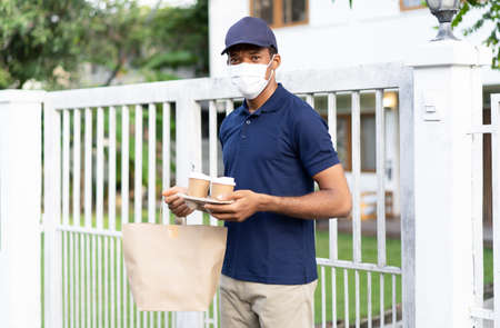 African American delivery man with face mask delivers takeaway food and coffee to customer, looking at camera.Delivery service under quarantine. Delivery Services During Coronavirus.COVID-19 epidemic