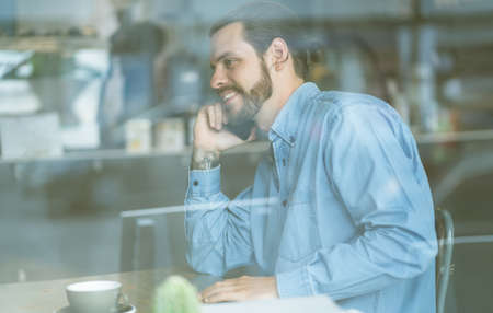 Stylish male freelancer talking on the mobile phone and smiling while sitting at table behind glass in cafe.Cozy office workplace.