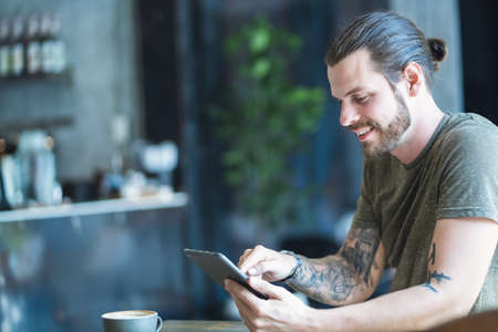 Handsome young beard man using focus on reading news and looking on digital tablet while sitting in cozy cafe. Freelance Work, Remote work, E learning Concept. 免版税图像