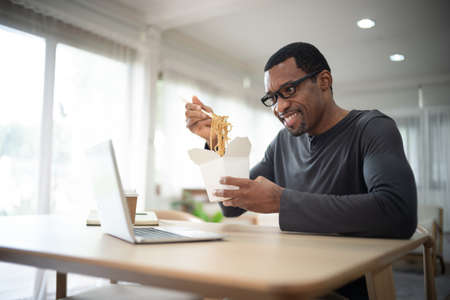 Handsome african american freelancer eating takeaway Asian food,spaghetti, with chopsticks.He online together with his friends on video call virtual party in quarantine time.Coronavirus outbreak 2020.