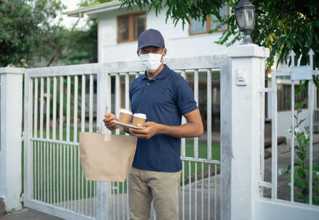 Portrait of handsome African American delivery man with face mask delivers takeaway food and coffee to customer.Delivery service under quarantine. Delivery Services During Coronavirus.COVID-19 epidemic 免版税图像