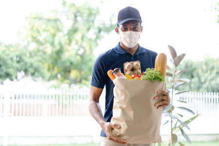 African American delivery man with medical mask holding fresh grocery in paper bag of food to customer home.Delivery service under quarantine. Delivery Services During Coronavirus COVID-19 epidemic. 免版税图像