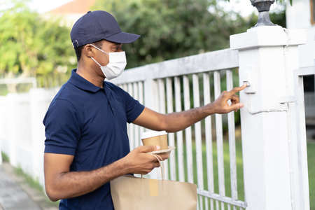 African courier guy wearing protective mask delivering coffee and food in disposable paper bag to customer home and ringing doorbell. Food delivery service under quarantine.During Coronavirus epidemic