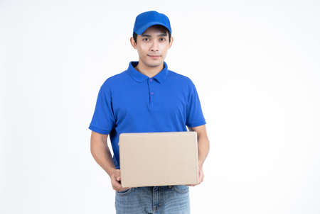 Young Asian delivery man in blue uniform standing with parcel post box isolated over white background.Delivery Service and Onlines shopping Concept. 免版税图像