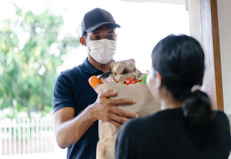 African American delivery man with medical mask delivering food to a woman at home.Online shopping and Express delivery. Under quarantine, disease outbreak, coronavirus covid-19 pandemic. 免版税图像 - 156988409