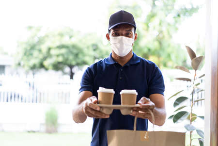 African American delivery man wearing protective mask carrying coffee and food in disposable paper bag standing in front of customer home.Food delivery service under quarantine.During Covid19 epidemic