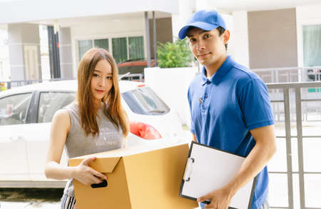 Smiling young Asian woman receiving package box from Asian delivery man in blue uniform at front of house and looking at camera.Delivery service , Onlines shopping concept.