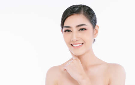 Beautiful young Asian woman with clean fresh skin and appealing smile isolated on white background. Facial treatment, cosmetology, spa, natural makeup beautiful concept.