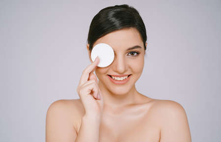 Beautiful young woman with clean perfect skin with holding round white cotton pad to her eye and smiling looking at camera  isolated on a gray background. Woman beauty face skin care concept.