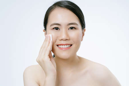 Beautiful young Asian woman with clean perfect skin with holding white cotton pad to her cheek and smiling looking at camera isolated over white background. Woman beauty face skin care concept. 免版税图像 - 156529095